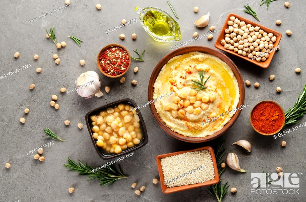 Stock Photo: Hummus topped with chickpeas, olive oil and green coriander leaves on stone table with different spices aside. Flat lay.
