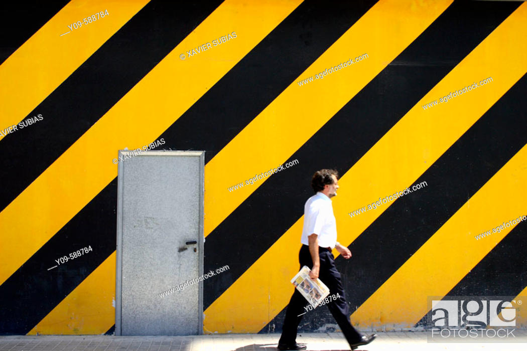 Stock Photo: Man walking in front of striped wall.