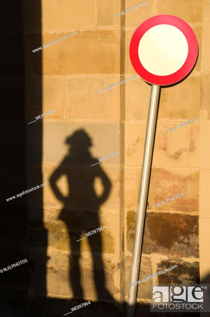 Stock Photo: Shadow of woman looking at traffic sign.
