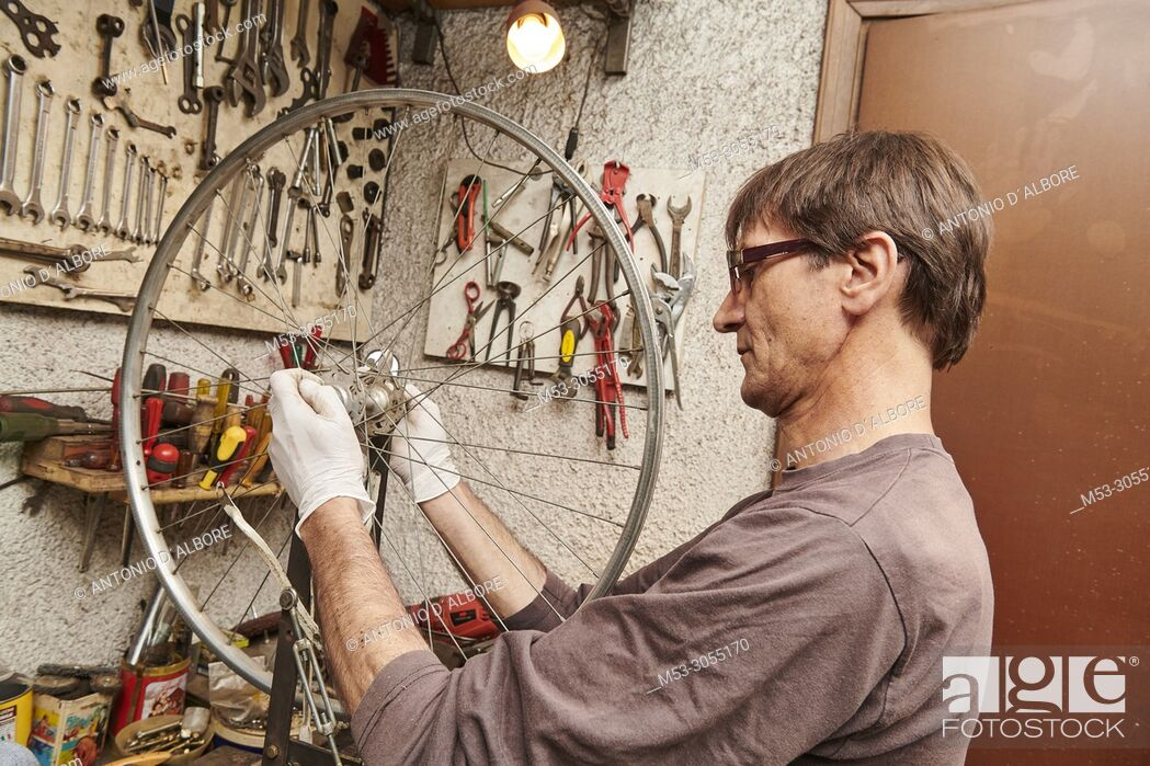 Stock Photo: A technician restoring a vintage bicycle.