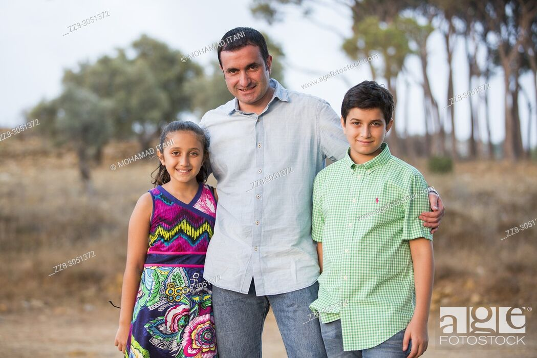 Stock Photo: man and his kids standing outdoors smiling.