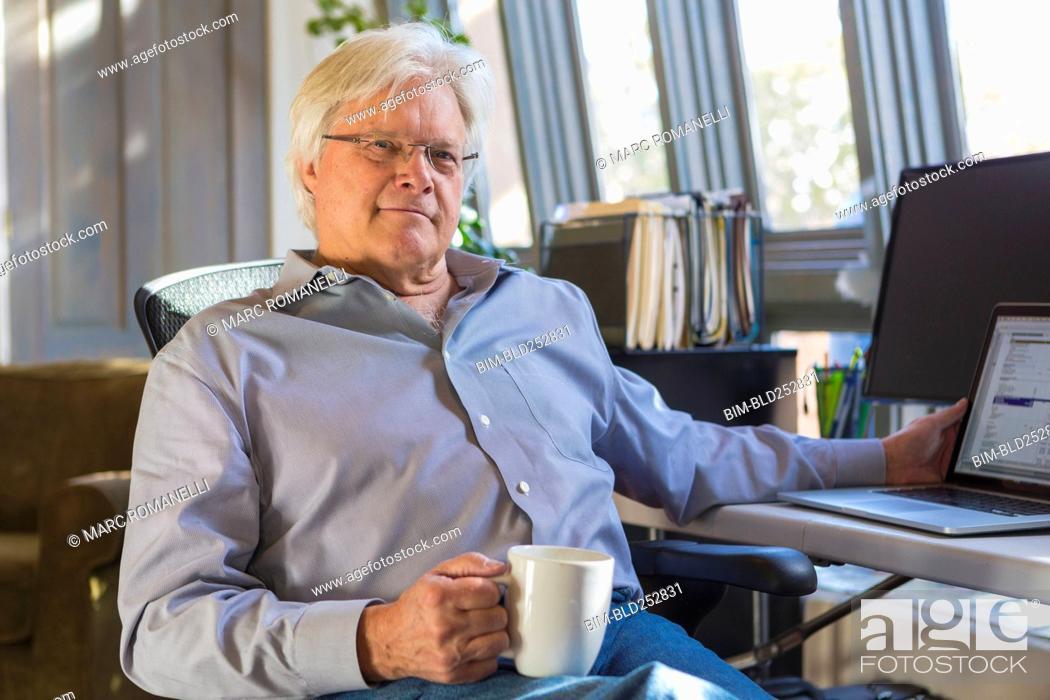 Stock Photo: Caucasian man drinking coffee and using laptop.