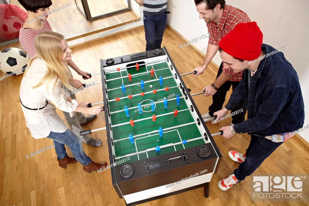 Stock Photo: Germany, Cologne, Men and women playing table soccer.