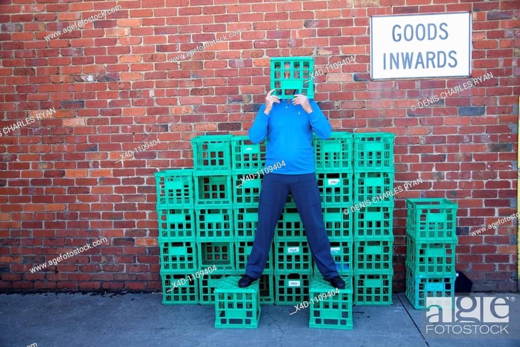 Stock Photo: Man on crates, covering his face.