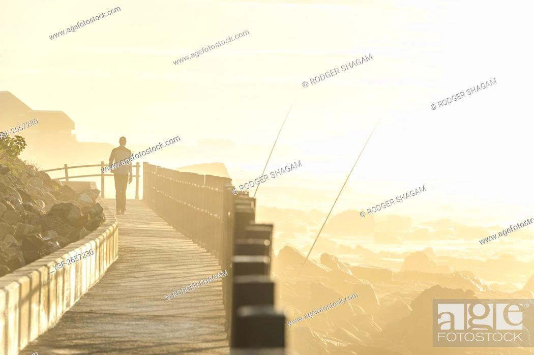 Stock Photo: Man strolling on a boardwalk as the sun rises over the sea. Muizenberg, Cape Town, South Africa.