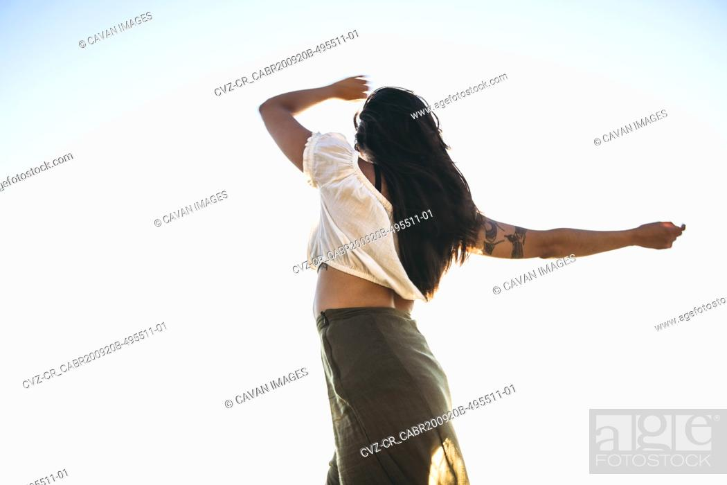 Imagen: Young Latina Woman dancing by the ocean at golden hour in summertime.
