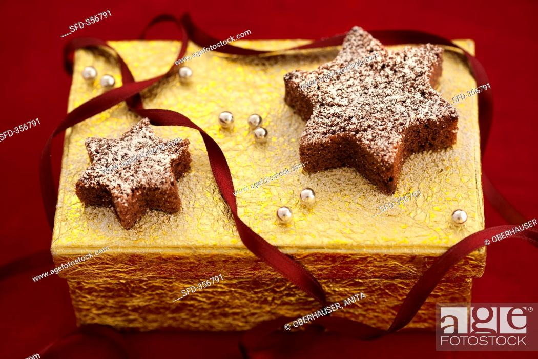 Stock Photo: Chocolate stars on a golden gift box.