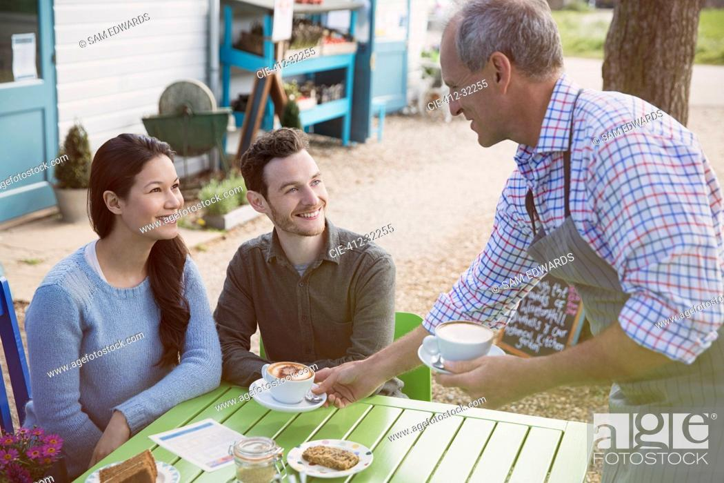 Stock Photo: Waiter serving cappuccinos to smiling couple an outdoor cafe.