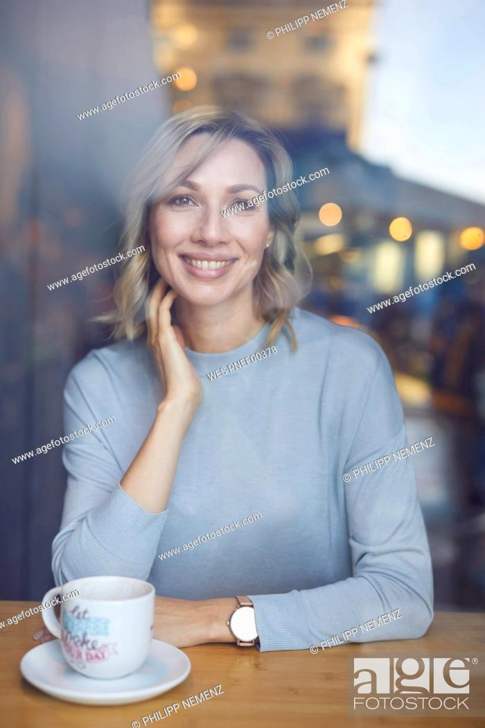 Stock Photo: Blond woman in cafe, behind window pane.