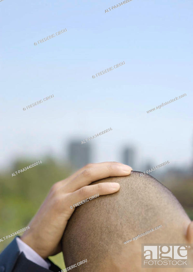 Stock Photo: Businessman holding head, cropped.