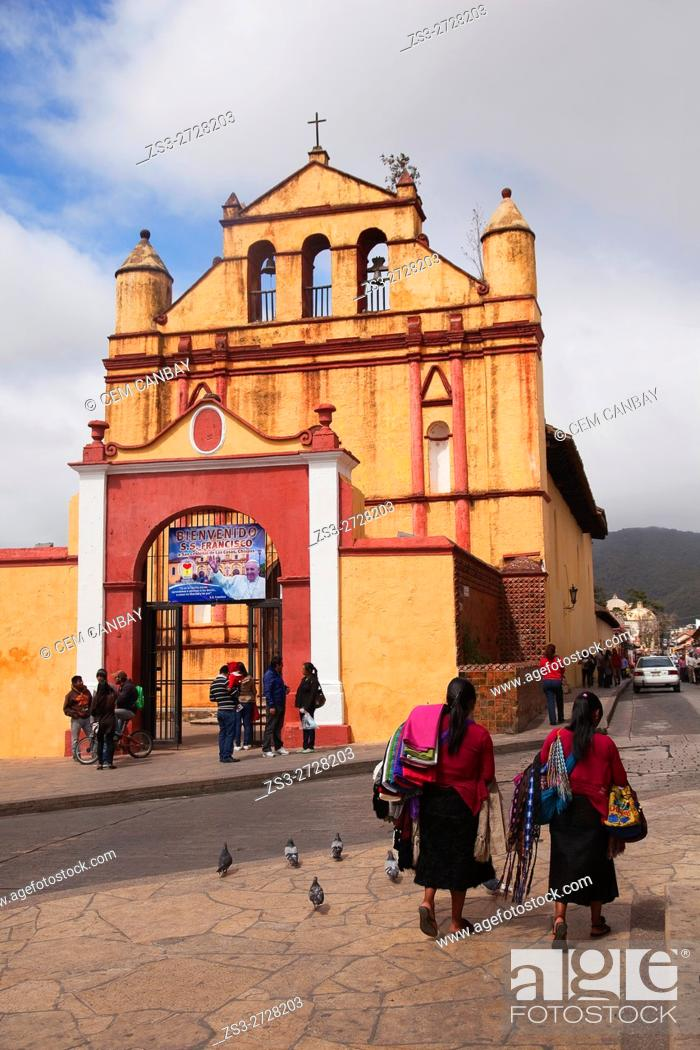 Stock Photo: Indigenous vendor walking in front of the Temple of St. Nicolas situated next to the Cathedral of San Cristobal, San Cristobal de las Casas, Chiapas State.