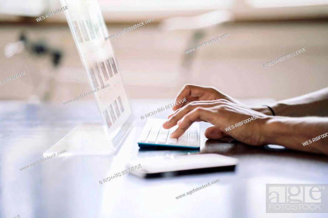 Stock Photo: Young man working on futuristic computer.