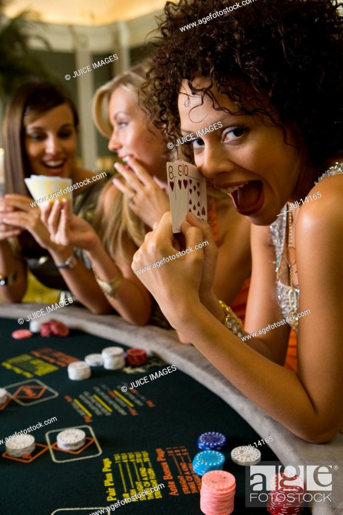 Stock Photo: Young woman gambling at poker table in casino, showing cards, smiling, portrait.