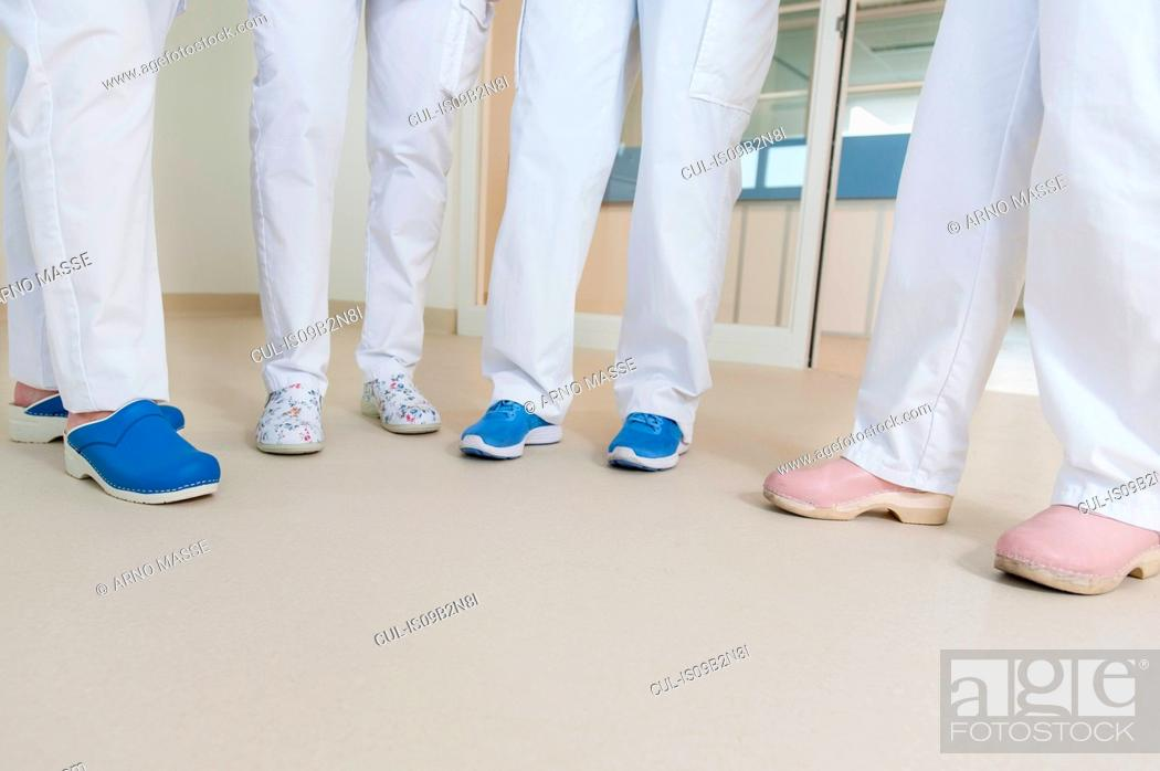 Imagen: Low section of group of nurses wearing surgical scrubs and clogs.