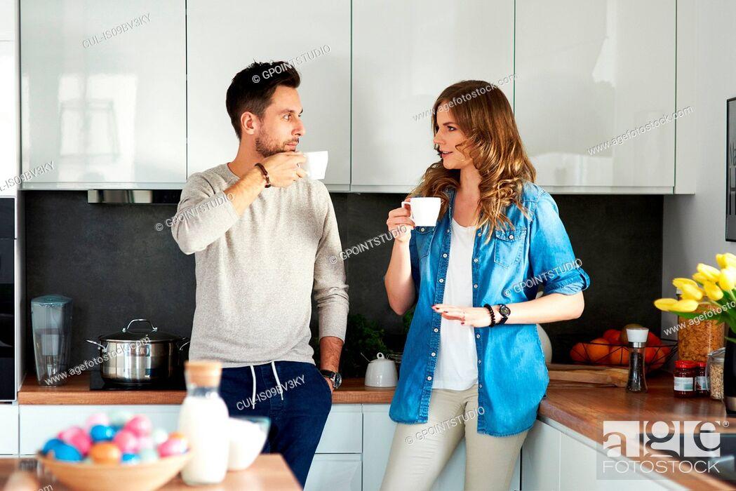 Imagen: Couple drinking coffee in kitchen.