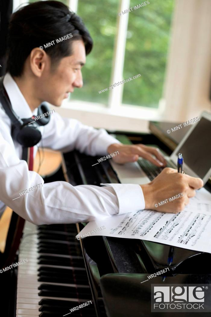 Imagen: Young man sitting at a grand piano in a rehearsal studio, annotating sheet music.