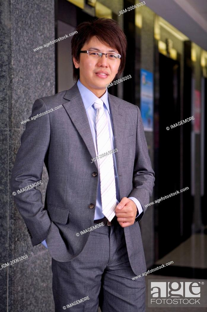 Stock Photo: Young businessman standing and looking at the camera with smile.