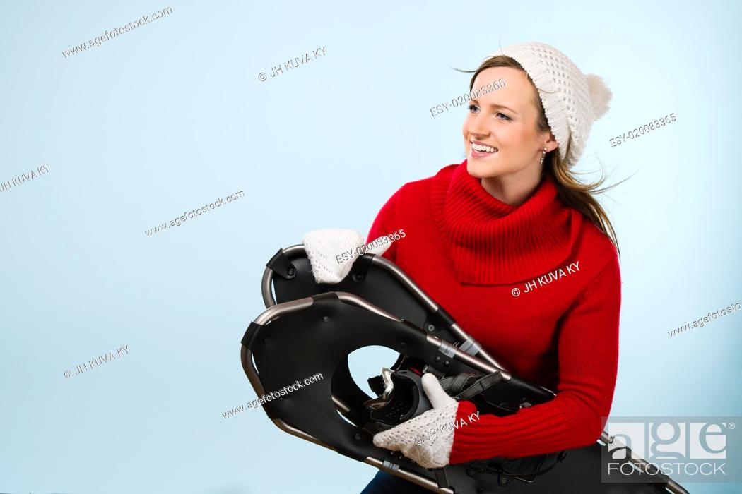 Stock Photo: Beautiful young sporty woman with snowshoes wearing a woolen outfit, horizon format.