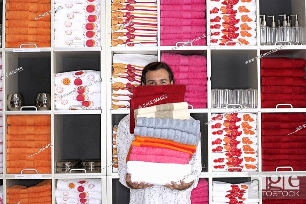 Stock Photo: Man shopping in department store, holding large pile of folded towels, face obscured, front view, portrait, shelves in background.