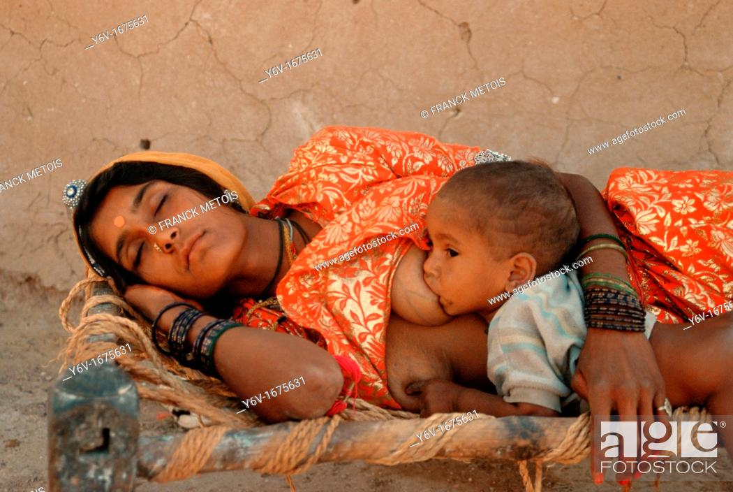 Stock Photo: A hindu woman is sleeping while her baby is suckling. From a village in Thar desert, Rajasthan, India.