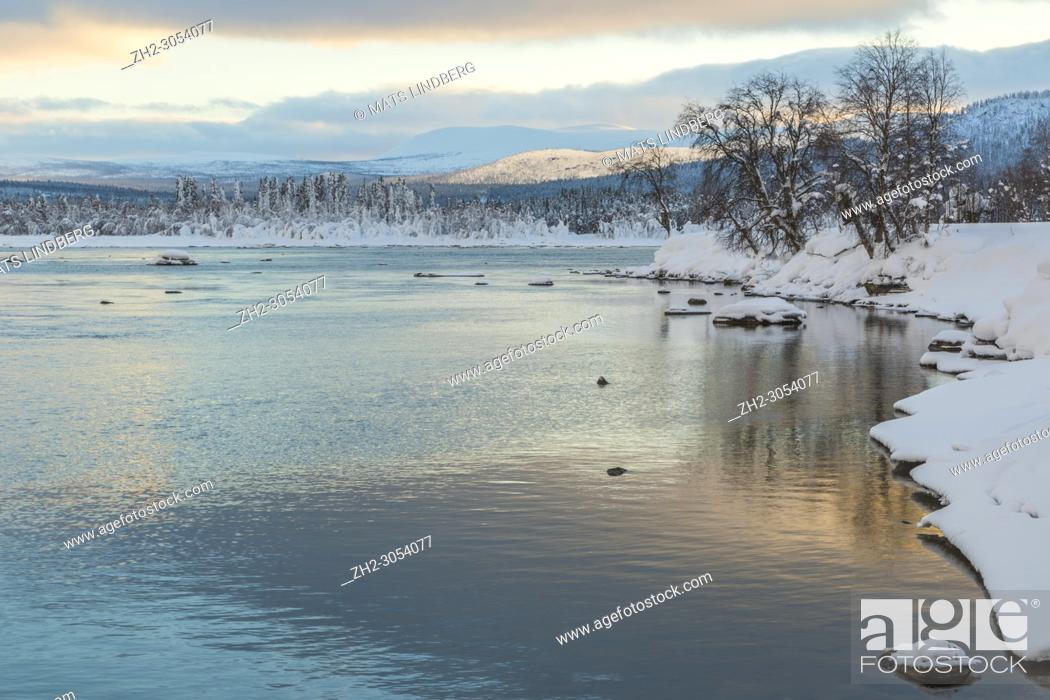 Stock Photo: Winter landscape in Tjåmotis with mountains in background, sun shining over the mountains, creek with open water, sky with nice colors reflecting in the water.