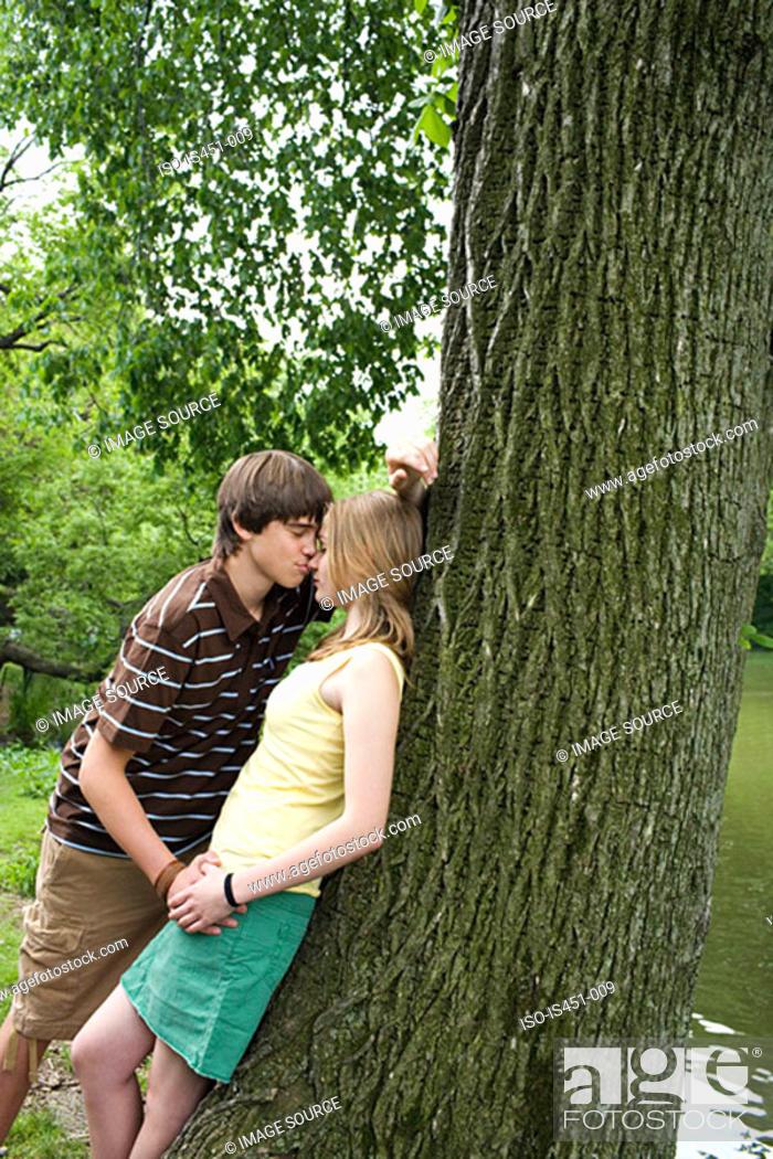 Stock Photo: Teenage couple kissing near tree.