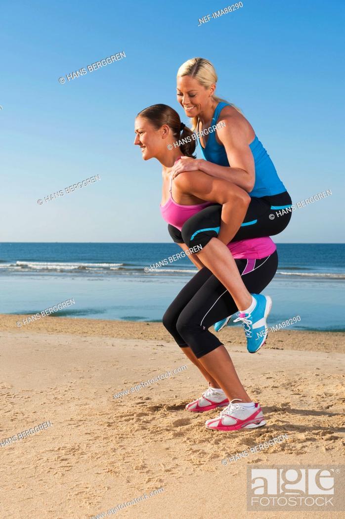 Stock Photo: Woman giving friend piggy back on beach.