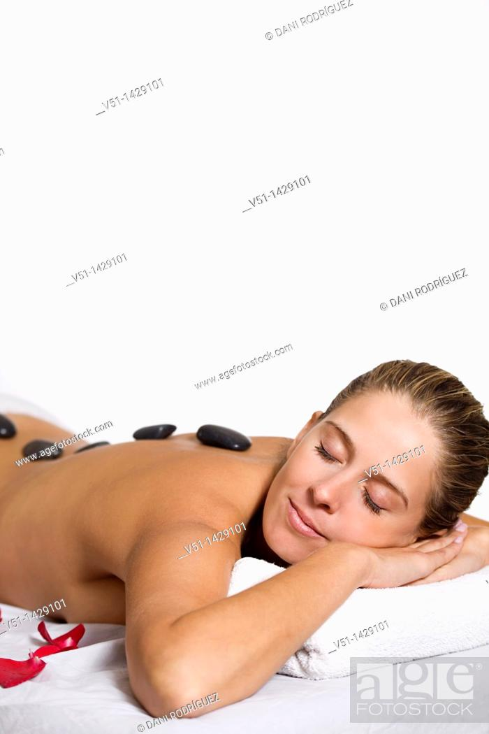 Stock Photo: Blonde woman in massage with stones und petals.