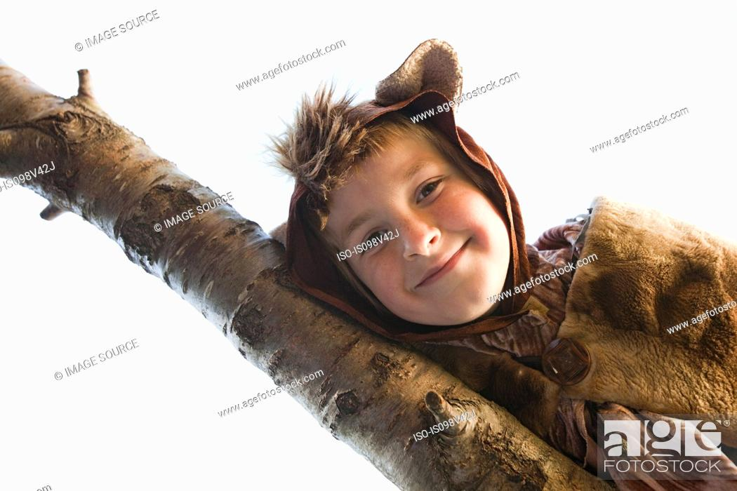 Stock Photo: Boy dressed up as bear on tree branch.