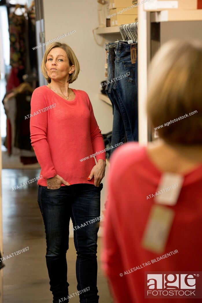 Stock Photo: Middle aged looking at herself in a mirror.
