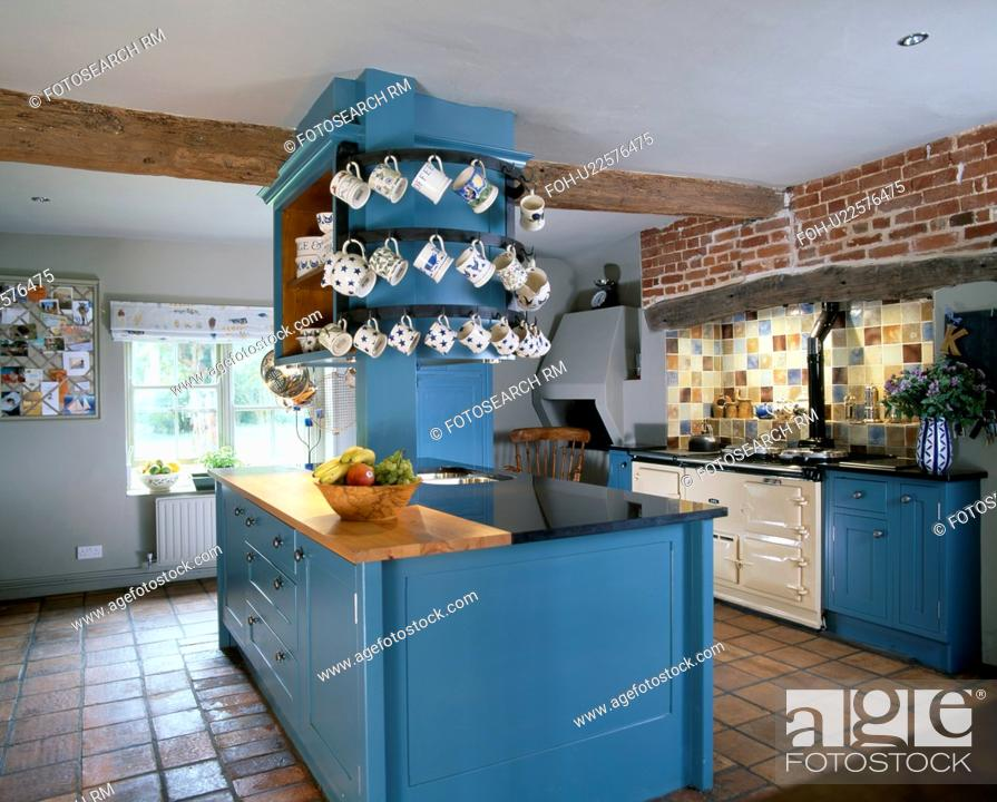 Stock Photo Cups On Shelves Above Blue Island Unit In Traditional Country Kitchen With Cream Aga Oven And Quarry Tiled Floor