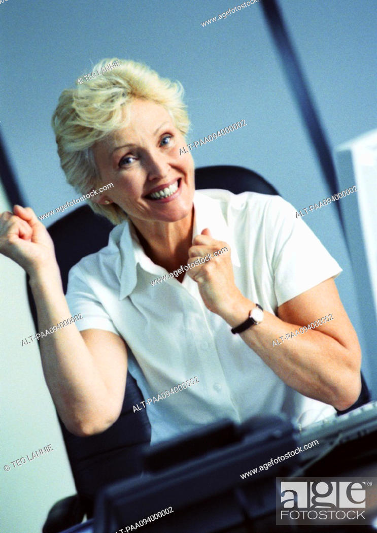 Stock Photo: Businesswoman raising fists and smiling, portrait.