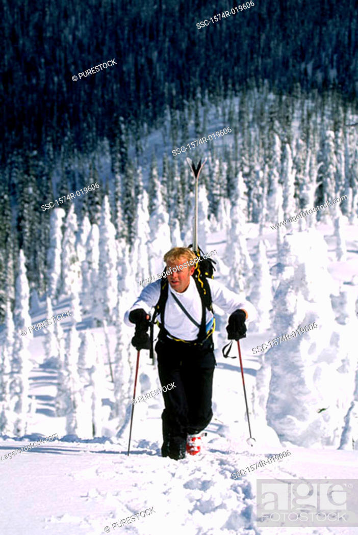 Stock Photo: High angle view of a mid adult man walking with skis in backpack.