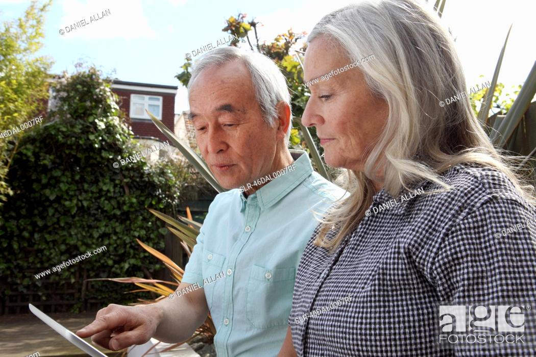 Stock Photo: Older couple using tablet computer.