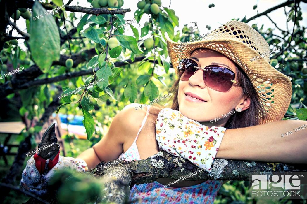 Stock Photo: Portrait of smiling woman with gardening gloves and pruner leaning on branch.