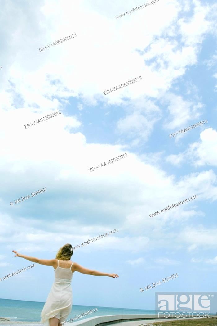 Stock Photo: Woman in sundress standing at the beach with arms outstretched, rear view.