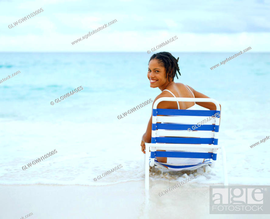 Stock Photo: Portrait of a young woman sitting on a lounge chair, Bermuda.