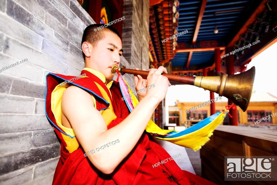 Stock Photo: Young man playing horn in a temple, Da Zhao Temple, Hohhot, Inner Mongolia, China.