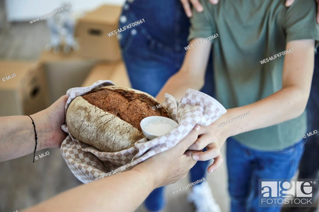 Stock Photo: Cropped image of hand with food for family while moving in new house.
