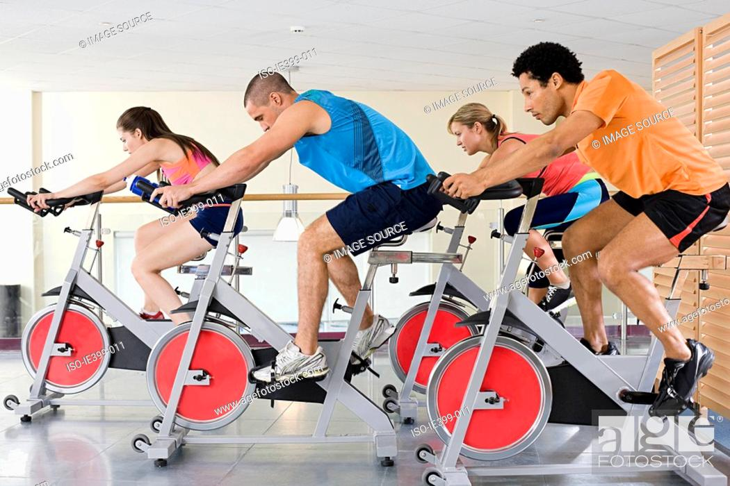 Stock Photo: People on exercise bikes.