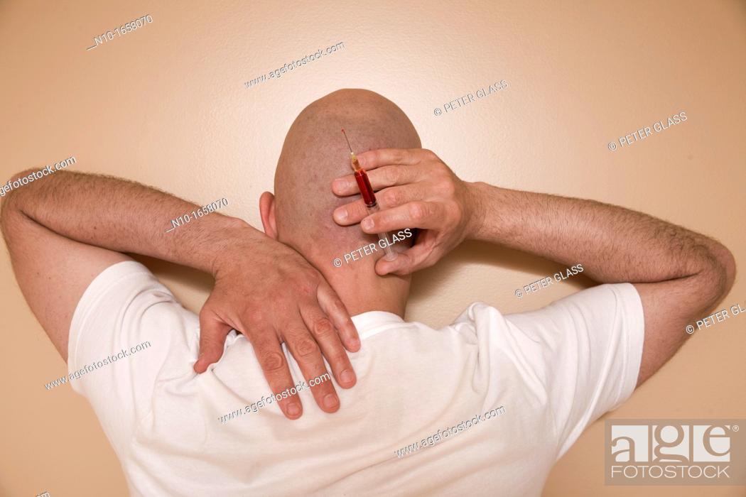 Stock Photo: Middle-age bald man holding a syringe.