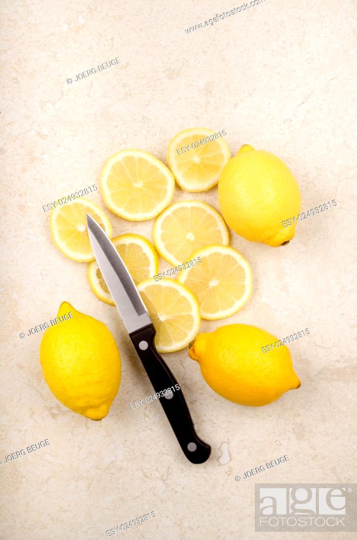 Stock Photo: fresh lemon, sliced lemons and a kitchen knife.