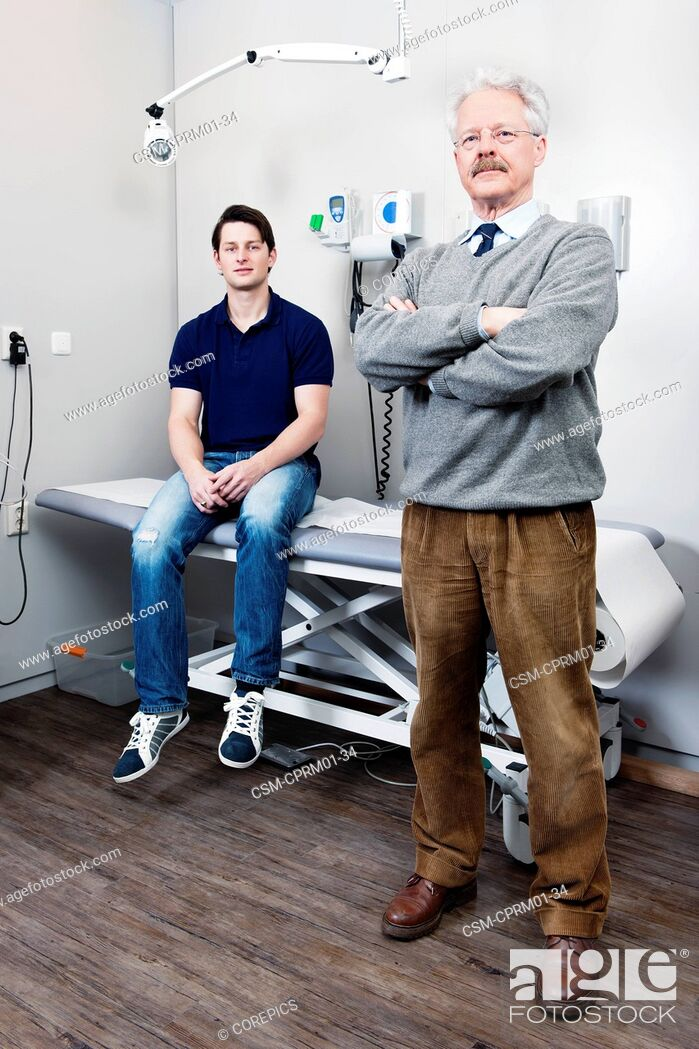 Stock Photo: Elderly doctor posing in front of his practice where one of his patients is sitting on the examination table.