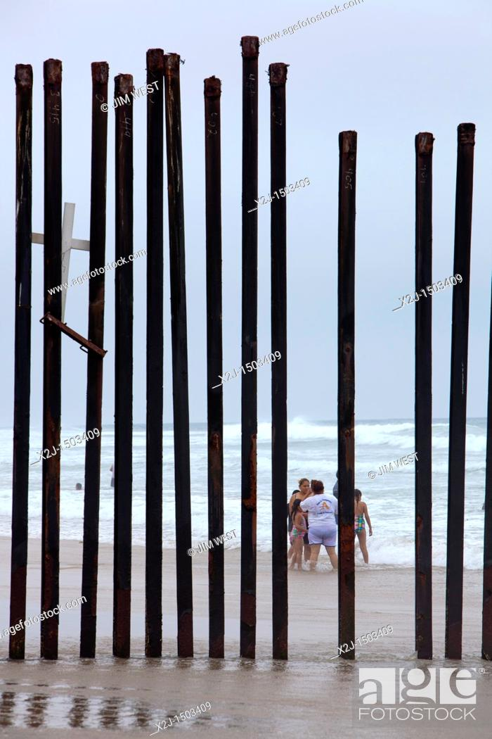 Stock Photo: San Ysidro, California - A fence at California's Border Field State Park separates the United States and Mexico on a beach at the Pacific Ocean.