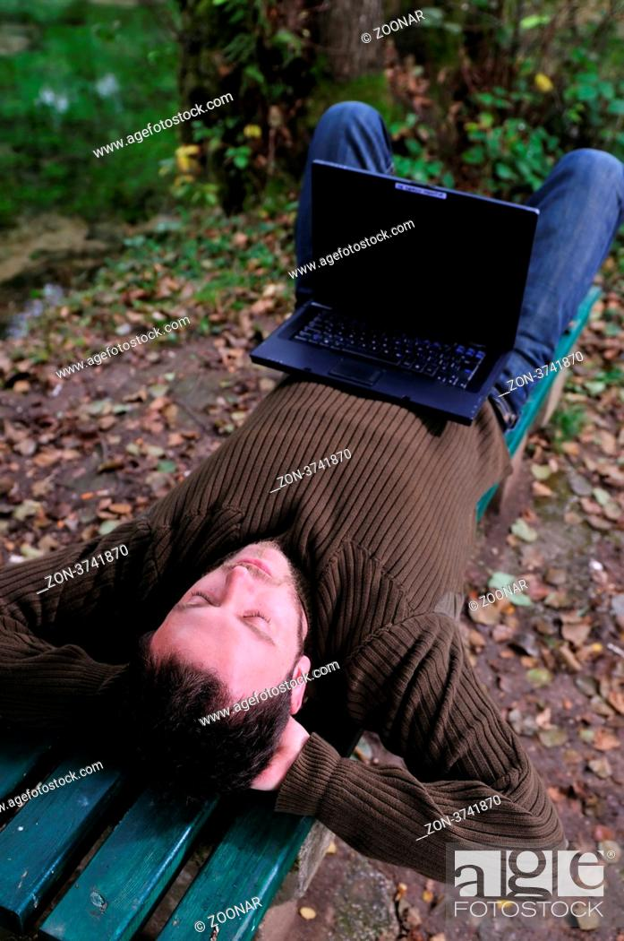 Stock Photo: one young businessman working on laptop outdoor with green nature in background.