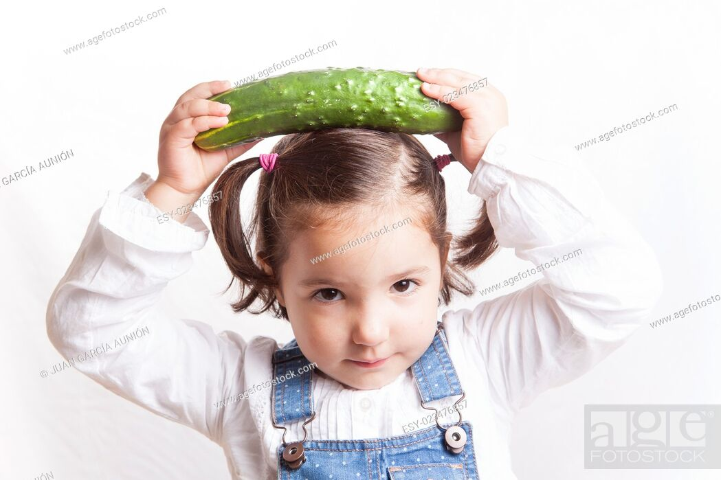 Imagen: Portrait of happy girl holding a cucumber. Isolated over white background.