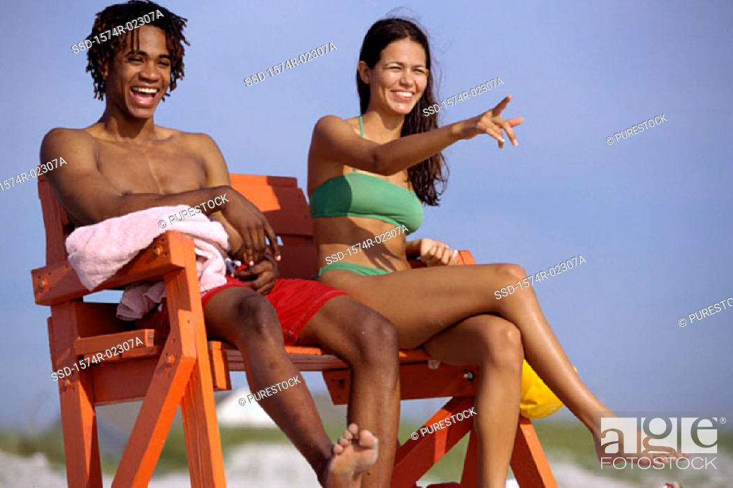 Stock Photo: Young couple sitting on a lifeguard chair on the beach.
