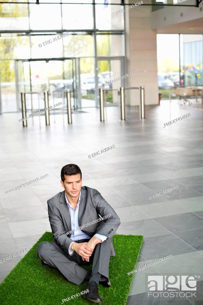 Stock Photo: Businessman relaxing on grass mat in an office lobby.