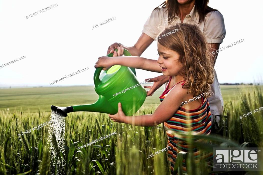 Stock Photo: Woman and child with watering can.