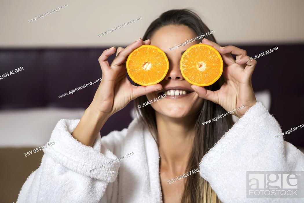 Stock Photo: Pretty young brunette woman in white morning gown sitting in hotel room and holding slices of orange near eyes.